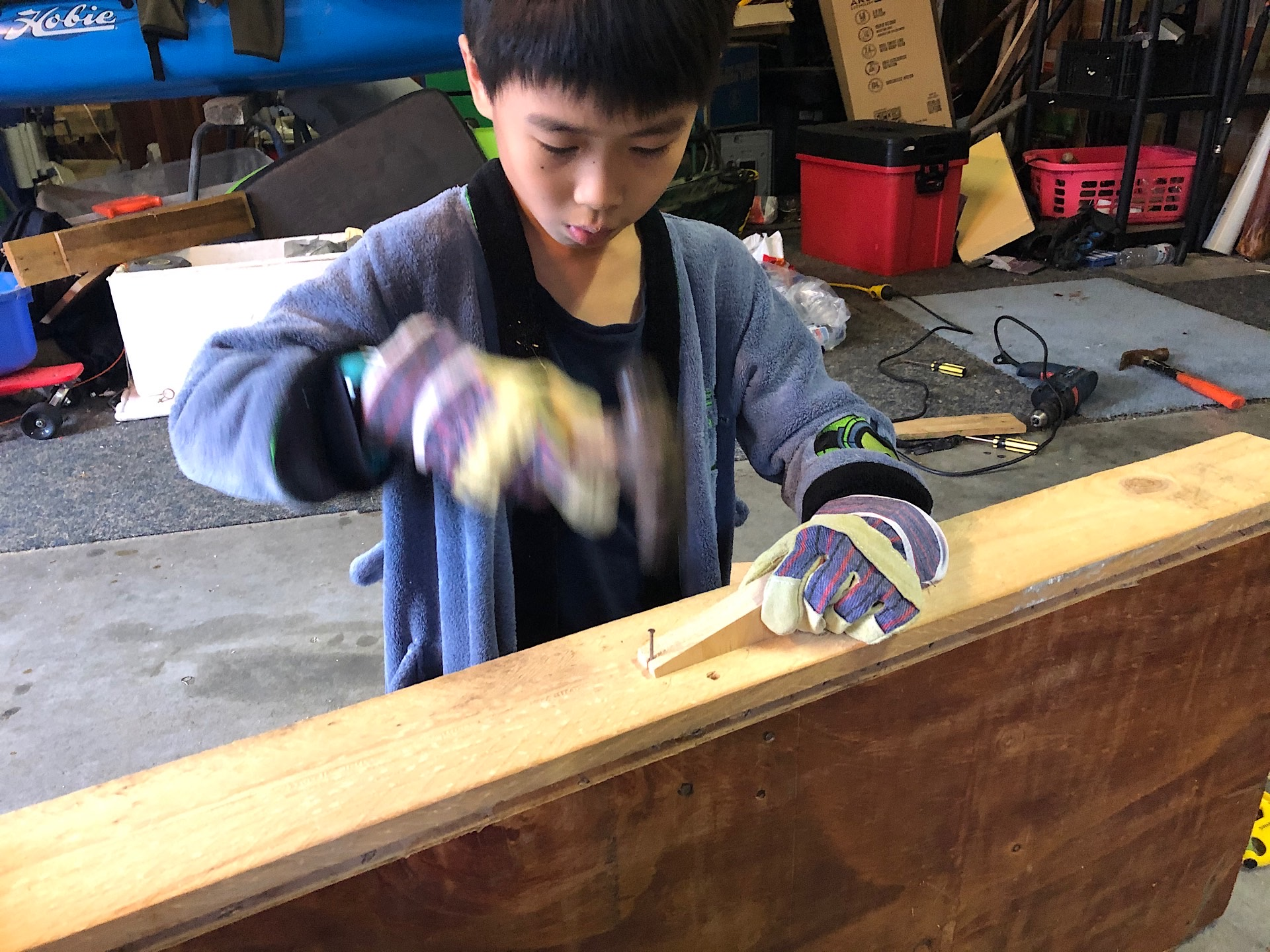 Thien-San is hammering a board to build his workbench