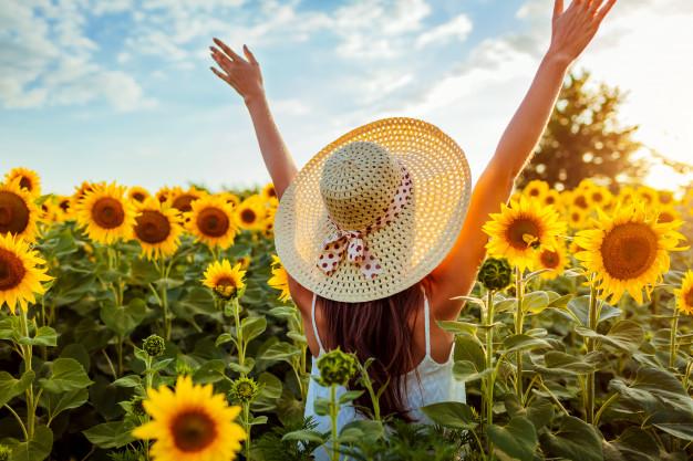 mujer-joven-que-camina-campo-floreciente-girasol-que-levanta-manos-que-divierte_106029-379.jpg