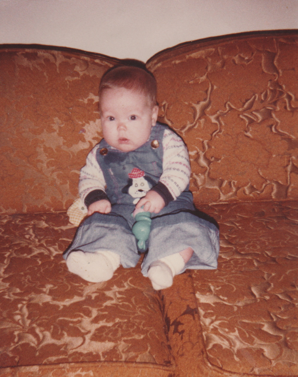 1981 maybe - Katie - Sitting on a couch.png