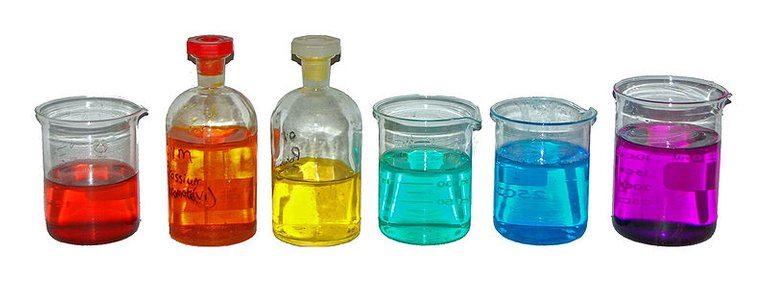 From left to right, aqueous solutions of: Co(NO3)2 (red); K2Cr2O7 (orange); K2CrO4 (yellow); NiCl2 (turquoise); CuSO4 (blue); KMnO4 (purple).