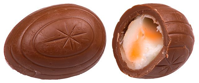 A whole and split Cadbury Creme Egg.