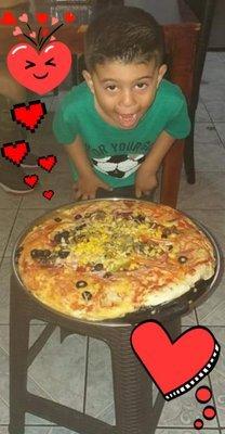 Mi pequeño feliz con su pizza/My little one happy with his pizza.