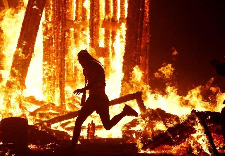 Burning-Man-participant-runs-into-the-flames-of-the-Man-Burn-at-the-Burning-Ma.jpg