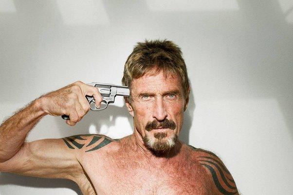 Shirtless John McAfee putting a gun to his own head.