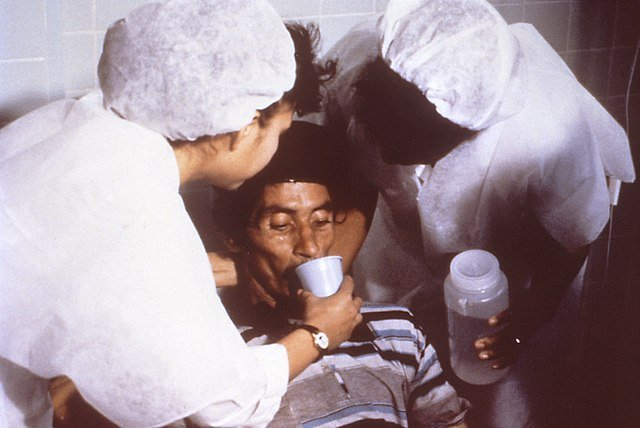 A cholera patient is drinking oral rehydration solution (ORS) in order to counteract his cholera-induced dehydration