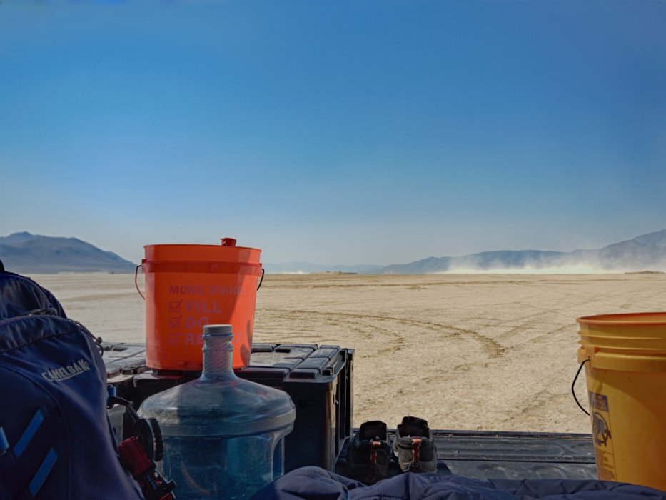 Truck glamping. The playa is alkali flat and hard on the skin. It was too hot for shoes, so I hid out in the bed of the truck watching and waving to the people driving and flying by.