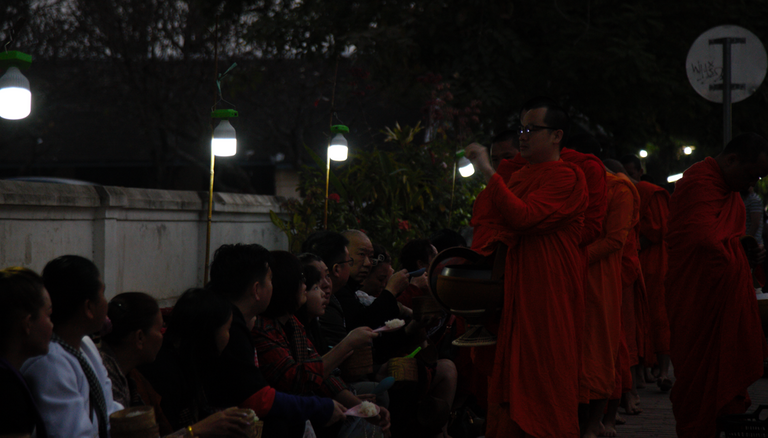 People sit along the road while giving food for the monk that pass by