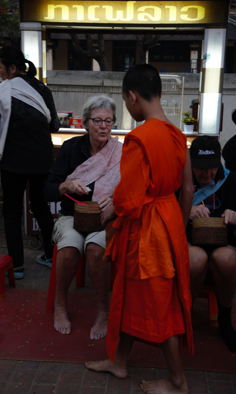 Some tourist join to give food for the monk
