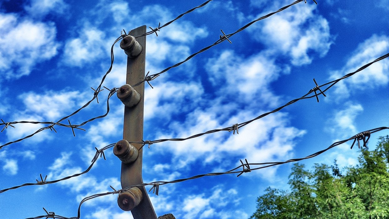 Barbed wire under a cloudy blue sky