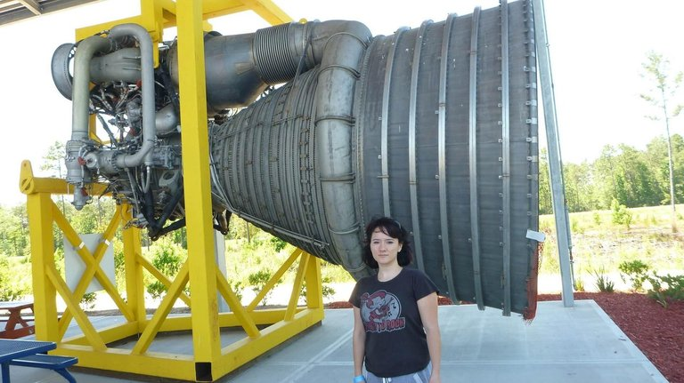 Amanda standing next to a rocket engine for size comparison