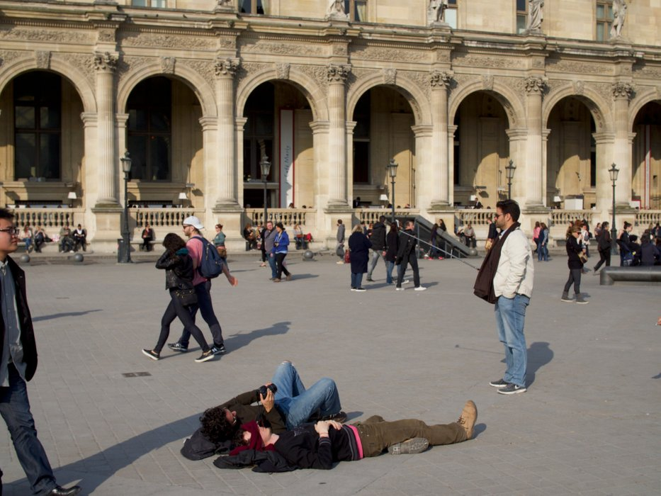 People making selfies everywhere on the square in front of the Louvre