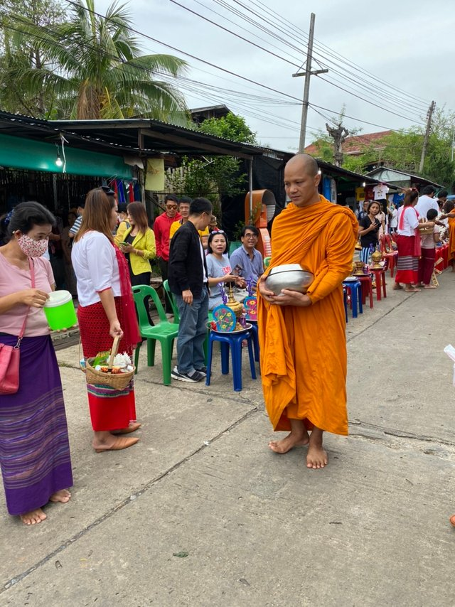 People are offering food to the monks