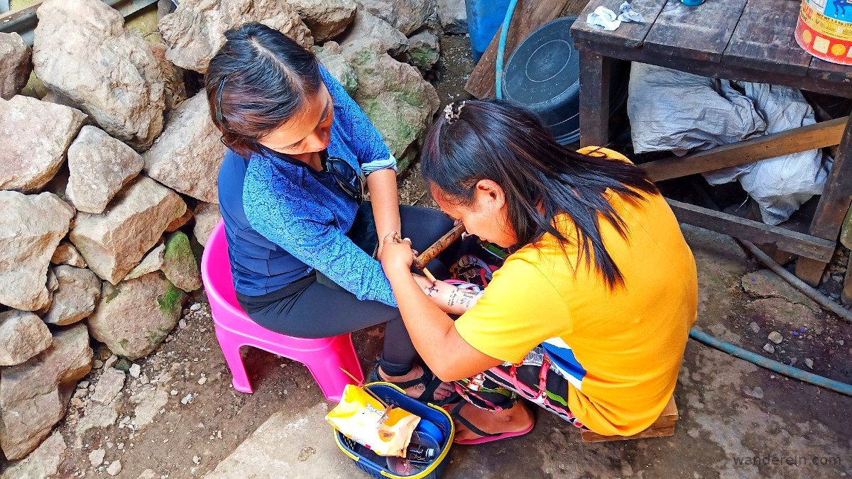 A young girl inks a compass tattoo using a pomelo thorn & pine soot ink