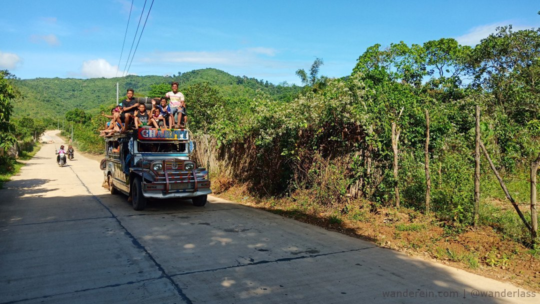Toploading on a Jeepney. Friendly locals wave at us