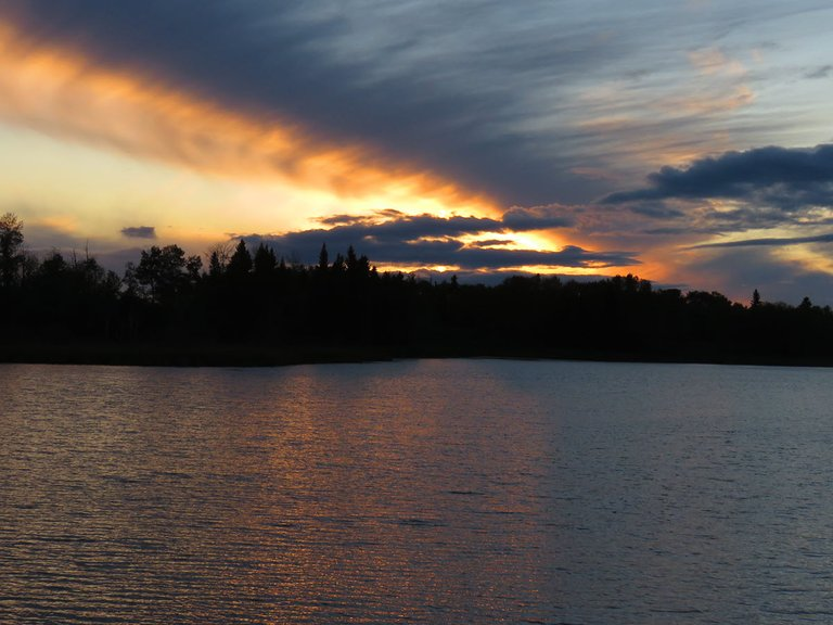 brilliant colors in streaks of clouds over pond.JPG