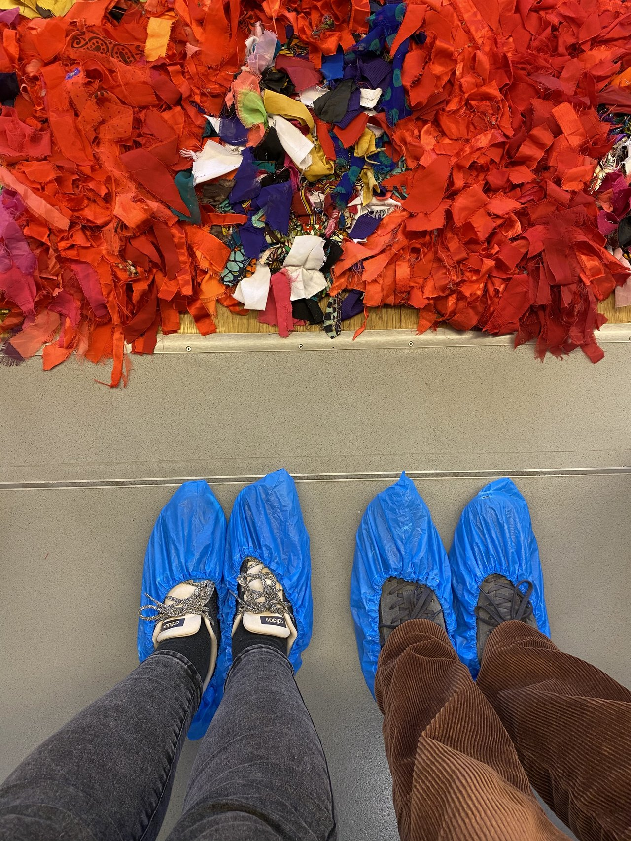 our feet clad in protective covers in front of a red carpet