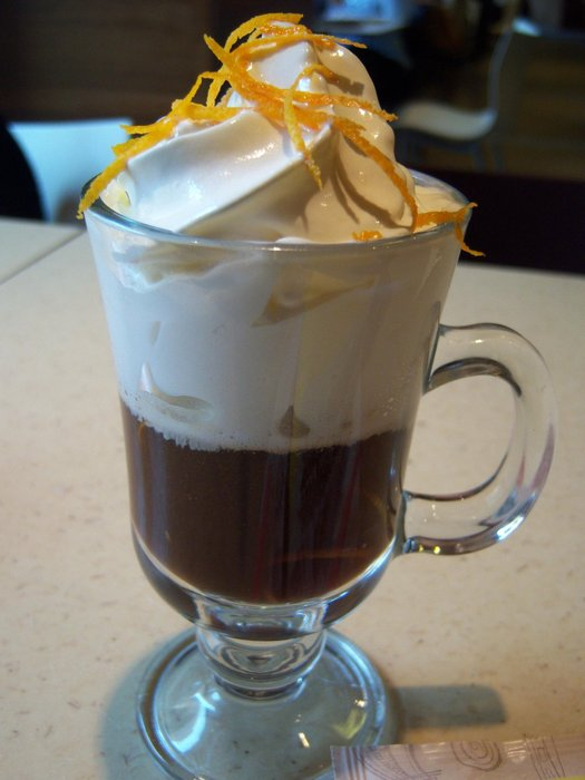 Delicious coffee with cream and orange zest in a local cafe